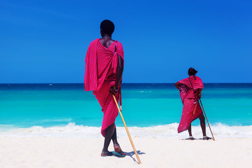 Two maasai warriors looking at ocean on white sand beach at summer.